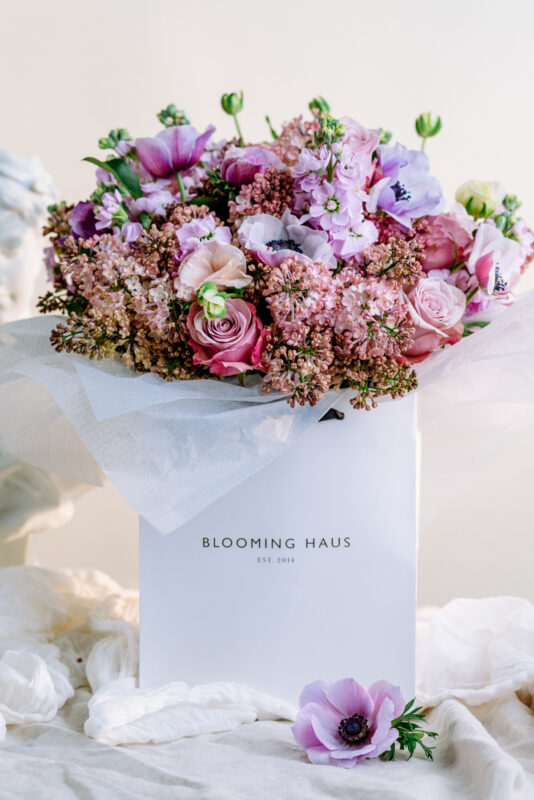 Anemone, purple roses, pink lilacs and purple stocks round bouquet by Blooming Haus