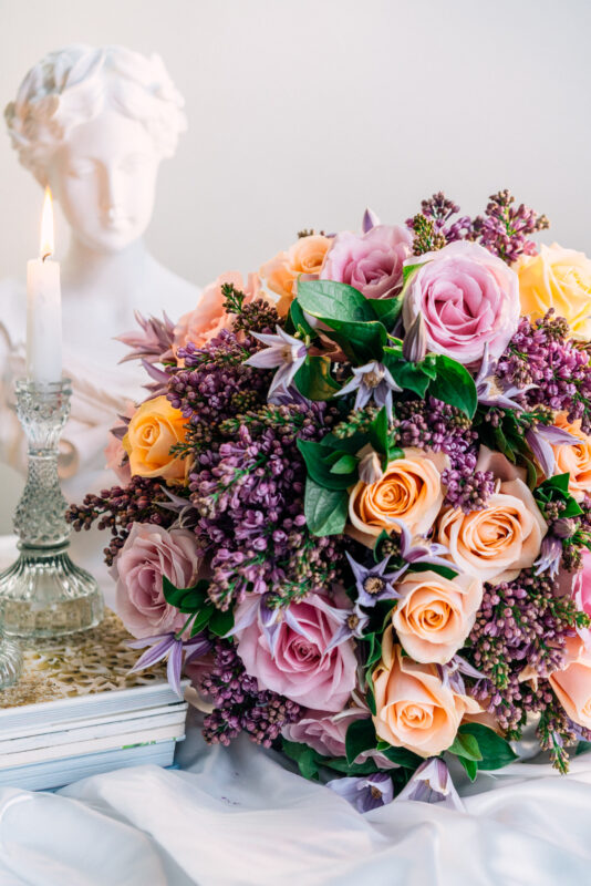 Purple lilac and peach avalanche roses round bouquet with clematis by Blooming Haus