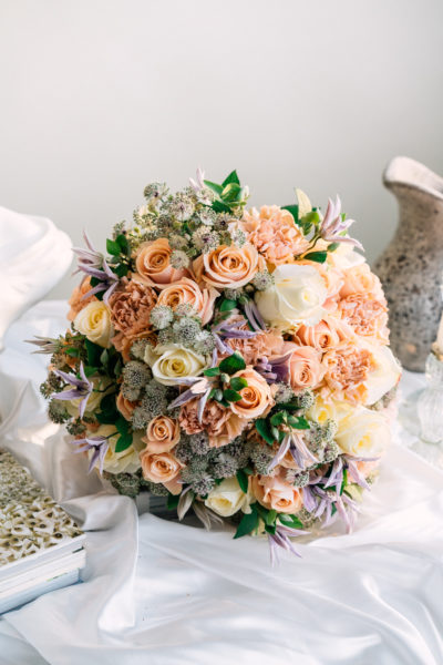 Pastel bouquet with peach, white roses, clematis and peach carnations