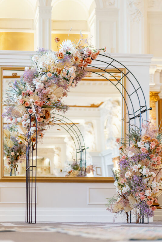 Peach, Pink and lilac flower arch with roses and carnations at Kimpton Fitrzroy Hotel wedding